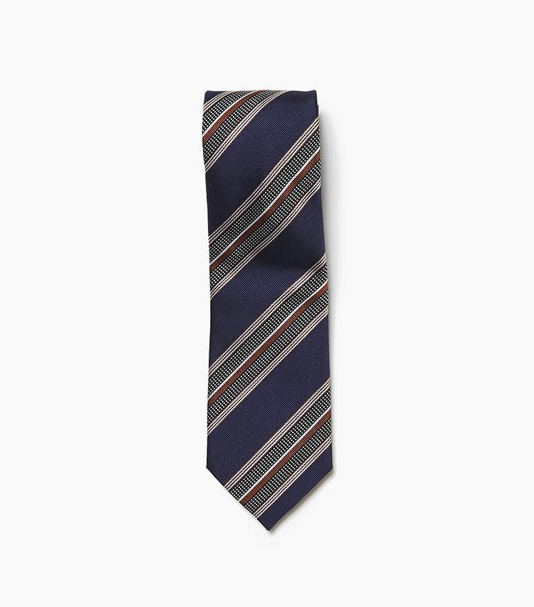 <b>9.ホリデー&ブラウンのストライプタイ</b><br />王道のネイビーをベースとしつつ、複数種の線と点を組み合わせた複雑なストライプ柄を配したジャカード織りのタイ。アーカイブから着想を得てデザインされた生地で、こちらもヴィンテージテイストが色濃く漂う一本だ。紺・茶・白からなる柄構成はどんなスーツにもマッチしやすく、着回しの強い味方になる。大剣幅8.5cm。1万6000円(アイネックス)