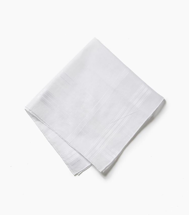 <b>11.カルロ リーバの白チーフ</b><br />世界最高級のシャツ生地としてお馴染みのカルロ リーバ。そのクオリティはチーフにもいかんなく発揮されていて、胸ポケットに挿した時のドレープ感は格別の美しさを誇る。こちらは同系色のチェック柄が織り込まれたもので、さりげないニュアンスを加えてくれるのも魅力的。四辺のハンドロールも丁寧で繊細な表情だ。1万円(アイネックス)