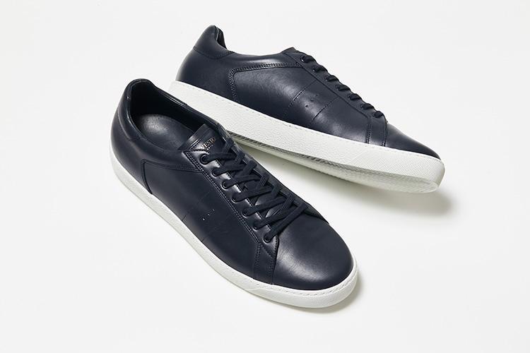 <strong>ジェイエムウエストン</strong><br />紺一色のボディとホワイトのラバーソールを合わせたシンプルなデザインが魅力。アッパーのステッチや、サイドにあしらった繊細な穴飾り、ソール周りの力強いサイドステッチなど、細部にまでこだわった意匠は仏の老舗シューメーカーならでは。スニーカーにおいても革靴同様の信頼を誇る。7万5000円(ジェイエムウエストン青山)