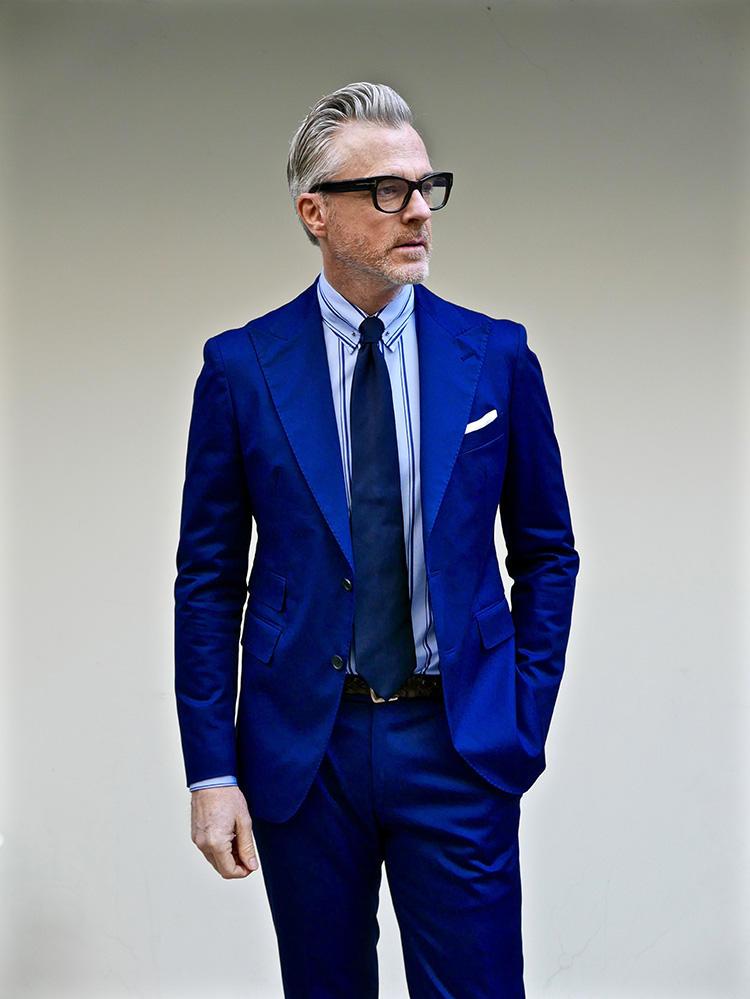 <strong>1.明るいトーンでアンチエイジング</strong><br />最速でイメチェンするなら、最も面積の広いスーツをテコ入れしよう。こんなインクブルーのスーツを選べば、顔色が明るく見えて溌剌とした印象に。デビッドは水色のオルタネイトストライプ柄シャツを選んだが、もちろん王道の白シャツでも十分イメチェン効果が臨める。
