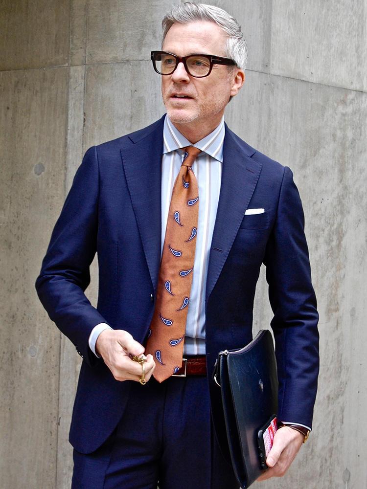 <strong>5.硬派な小物で固めて知的ミドルに</strong><br />ネイビースーツはいわば白いご飯。おかずとなる小物の組み合わせ次第で、さまざまな味の定食に仕上がる。セルフレームの眼鏡、TVホールドですっきり挿した白チーフ、革のクラッチバックなど、手堅い小物でまとめれば、万人から好感を持たれるコーディネートは容易につくれる。