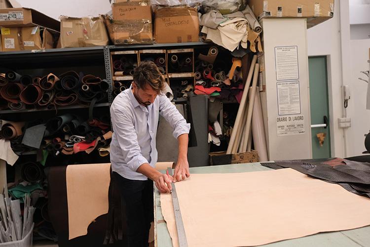 17歳のときにベルトなど革小物作りの工場に入り、職人歴20年の大ベテラン、モリスさん。まずは大判の革から端を直線に手裁断。