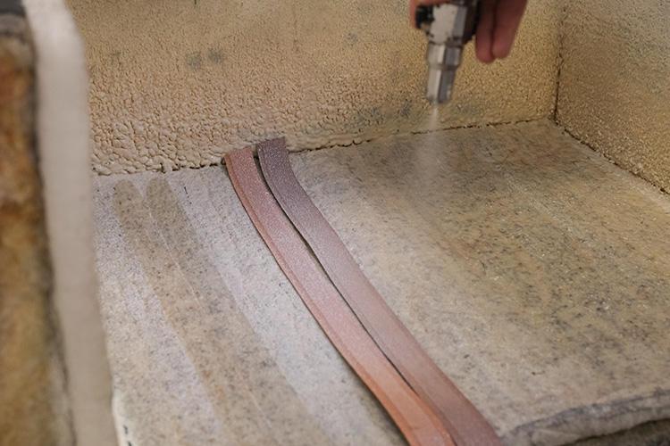削いだ2枚の革を貼り合わせるスプレー。環境を意識し、水を主体とした糊を使っている。