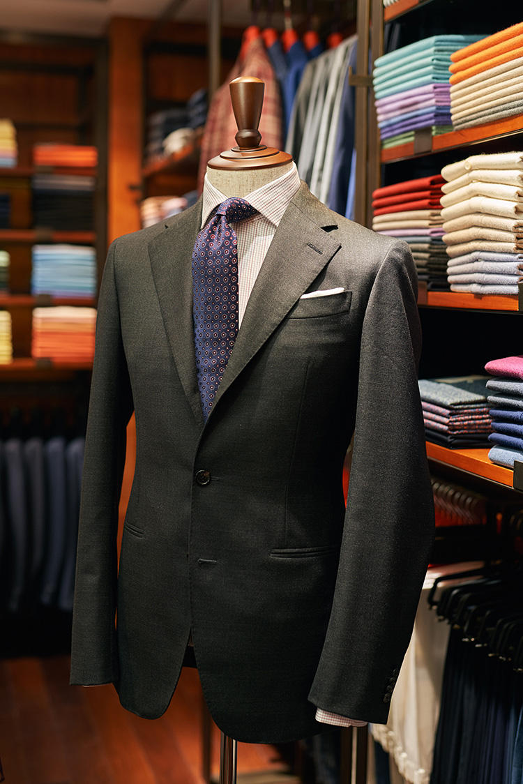 <b>平日のビジネスマン向け、堅めのグレーのクラシックなスタイル</b></br>パッドなしで肩周りもコンフォート、少しシャツスリーブになったイタリア的スタイルのスーツ。ジャスティン氏も着ているので「ジャスティン・モデル」と呼んでいる。この形をベースにビスポークも出来る。「ちょっと面白みを出すため、シャツはチェックにしました。シャツ、ネクタイとも、個人的に気に入っているバーガンディと青の組み合わせを取り入れました」