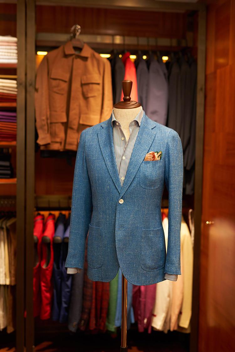 <b>ドレスアップとカジュアルの中間、カジュアルフライデー的スタイル</b></br>ドラッパーズのウールシルク混生地のジャケットに、新しい襟型のシャツをIN。「カジュアルだけどドレスアップした感じのルックです。最近は、証券会社などのビジネスマンでもこういった装いの人が増えてきましたね。シャツは新しい襟型です。以前は、既製のシャツはもっとイギリスっぽいのが多かったんですが、ここ数年は銀行などでもノータイOKになったりと仕事服に変化が出てきました。そこでネクタイをしなくてもジャケットの下で襟が立ちやすい、もう少しヨーロピアン的なシャツの襟型を作りました」(ジャスティンさん)