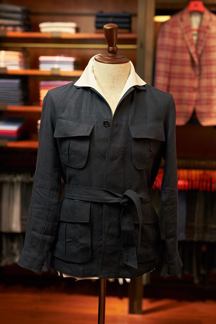 <b>「ジャングルジャケット」のウィークエンドスタイル</b></br>サファリジャケットにいろんなディテールを付け加えて変化をつけた今季の新作「ジャングルジャケット」。アメリカのベトナム戦争時のアメリカ軍のアーミージャケットのスタイルを取り入れ、少しエレガントさを加えるために、ベルトも付け加えた。サファリジャケットと同じように背中にアクションバックも。既製でもあるし、これをベースにMTMも可能。中のポロシャツはワンピースカラーで、襟を出しても着られる。