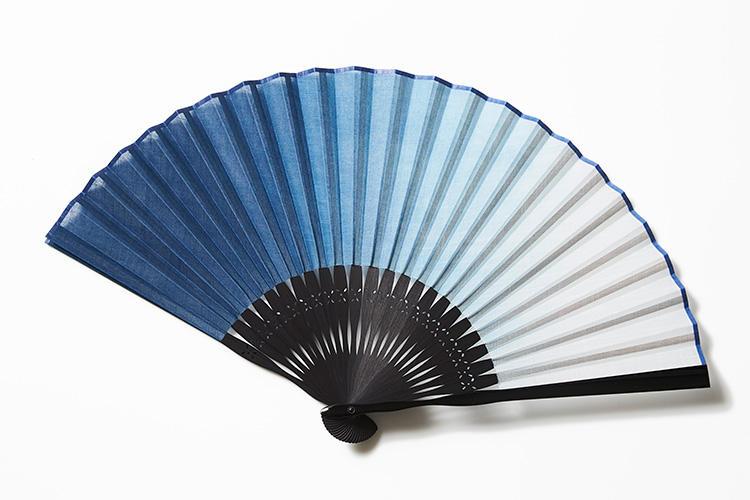 <strong>白竹堂</strong><br />天然藍の原料である、すくもと灰汁(あく)を使って醗酵させた液体で染める本藍染が見事な京扇子。化学薬品を一切使用しない天然素材のみの伝統的な技法を駆使して染めた藍本来の深くて上品な色合いが印象的だ。ほんのりとグラデーションを掛けた、ぼかし染めも涼やかな雰囲気を添えてくれる。1万円(白竹堂京都本店)
