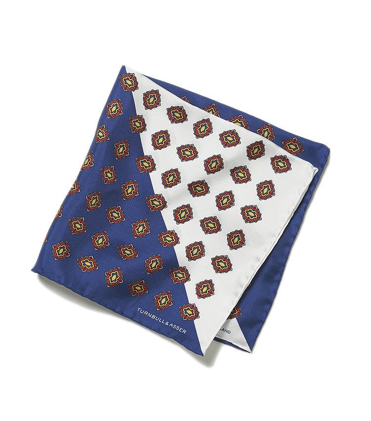 <b>12.ターンブル&アッサーのメダリオンチーフ紺×白</b><br />最高級シルクを使用し、上品な色柄をのせたチーフは、手仕事による縁のロール仕上げまで繊細。胸元からほんの少しだけ覗かせるだけでも、華やぎを添えられる。1万4000円(ヴァルカナイズ・ロンドン)