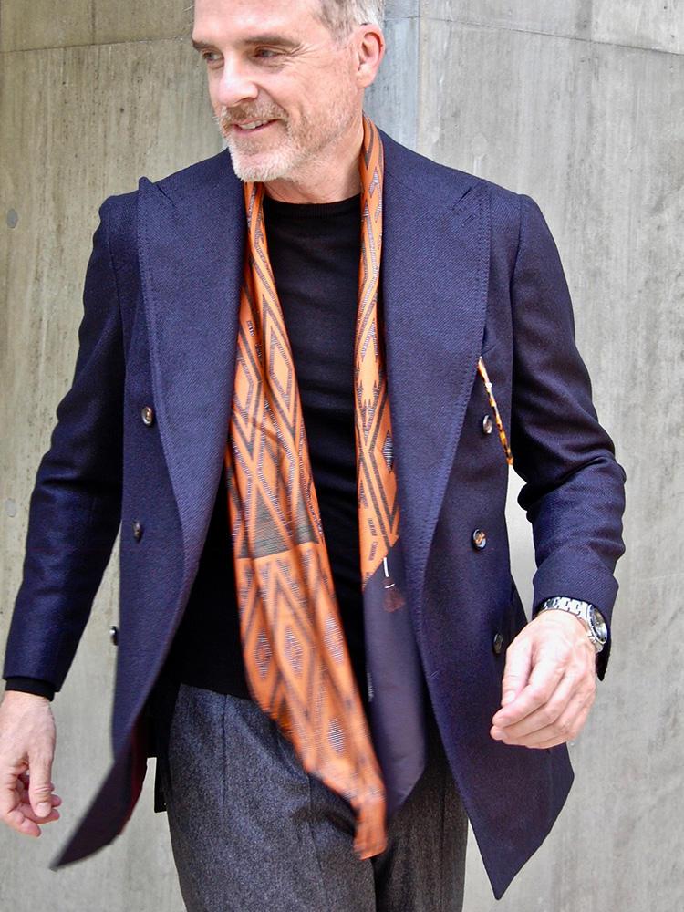 <strong>1.エスニック柄のスカーフをスパイスに</strong><br />ネイビーのジャケットとニット、グレーのパンツという至って普遍的な組み合わせに、民族調柄のオレンジスカーフで自分らしさを演出。スカーフと同系色のべっ甲眼鏡を胸ポケットから覗かせることで、全身の統一感を高めたテクニックも見事。