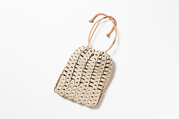 <strong>イル ミーチョ</strong><br />フィレンツェ在住の革職人、深谷秀隆氏が手掛けるイルミーチョの巾着バッグ。滑らかで上質な山羊革を一つ一つ丁寧に編み込んでおり、使い込むほどに増す風合いが魅力だ。撚ったレザーのハンドルは、繊細ながら耐久性が高い。スマートフォンや財布などを入れるのに便利なサイズ感。ナチュラルな色合いもコーディネートを選ばず休日に気軽に使える。3万2000円(ストラスブルゴ)