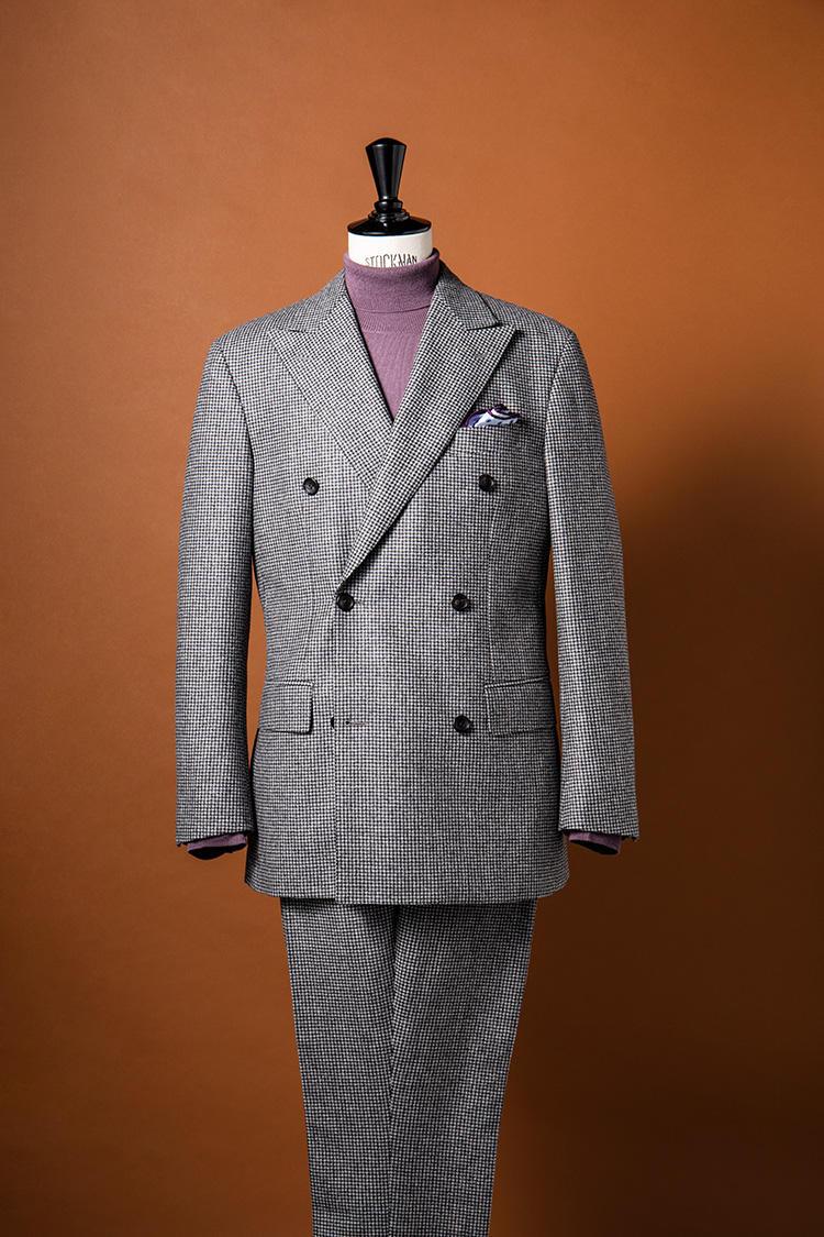 やや起毛した千鳥格子柄のダブルスーツに、ハイゲージウールの淡いパープルのニットをひと挿し。クラシックなスーツも、一気に休日の華やかなドレスアップスーツスタイルに変わる。スーツ17万円、ニット2万3000円、チーフ5000円/ポール・スチュアート(ポール・スチュアート 青山店)