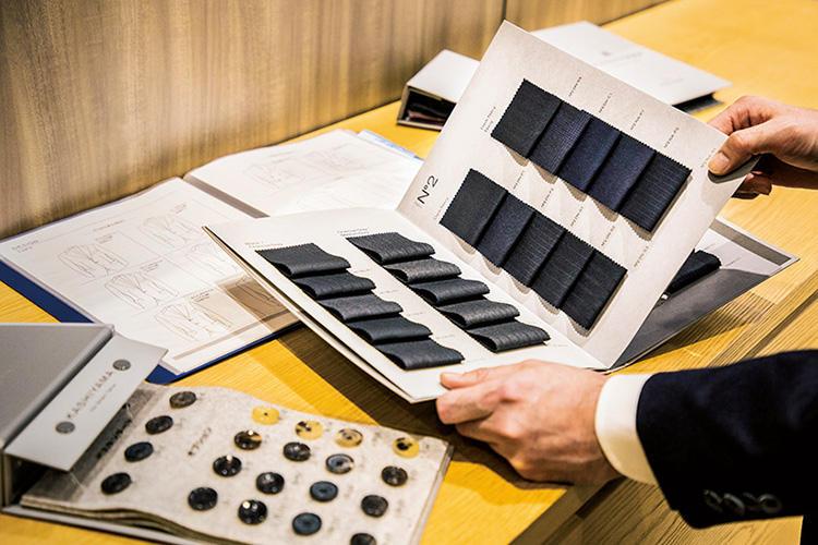 <font color=red><b>2:型選び・採寸</b></font><br><br><b>ベース型に生地、ボタンなどを細かくカスタマイズ</b><br>当日はフロントデザイン8種をベースに、生地やポケット等の仕様を決定。採寸(写真上)はゲージ服を羽織りながら。体型補整ができる箇所も60と充実している。