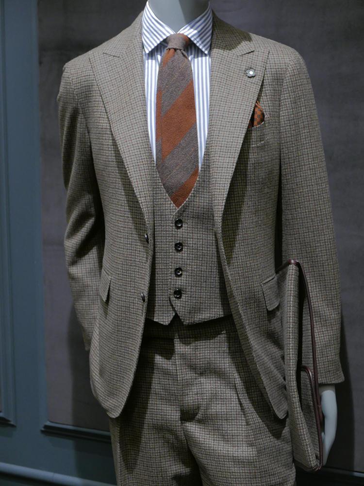 ラルディー二。シングルピークトのスーツやロンドンストライプのスーツで英国感。スーツの細かなチェックにブラウンのペーンが入っており、このブラウンと、ネクタイやチーフのオレンジが絶妙に合う。