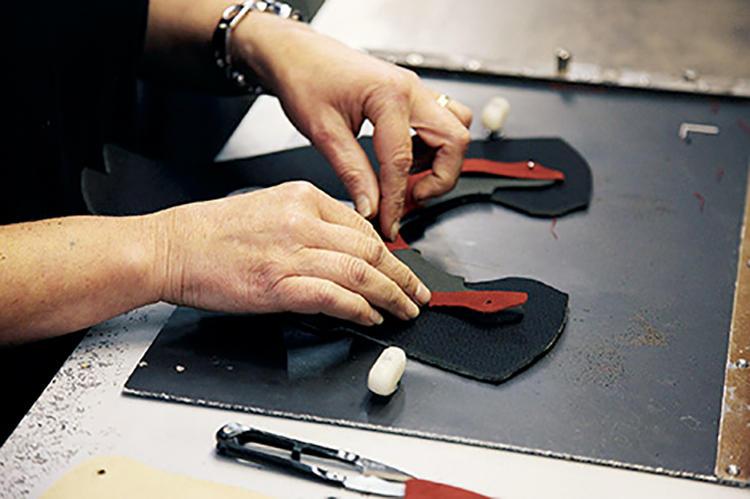 写真は英国フリンビー工場の生産風景。革の裁断は仕上がりを左右する重要な工程で、繊維が伸びる方向まで見極めた裁断が求められる。