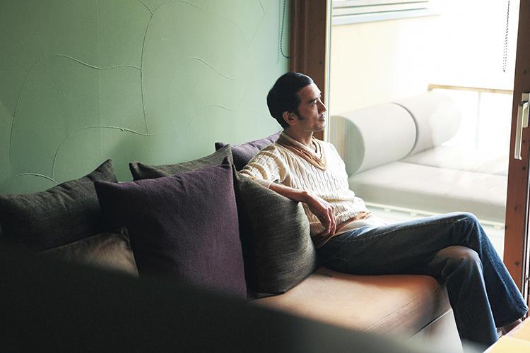 ソファに座るチルデンニットを着用したモデル