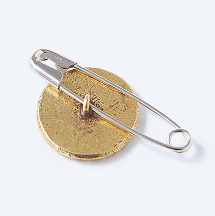 <b>1 ボタン裏側のループに安全ピンを通す</b><br />裏側に糸通しのループが付いているものを使用。ここに安全ピンを通すだけだ。ピンが小さすぎるとボタンが取れてしまうので注意。
