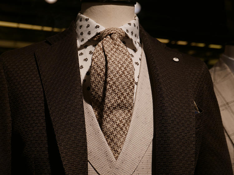 【L.B.M.1911】ダークブラウンのジャケットにブラウングラデーションを効かせた組み合わせ。ジャケットの織り感に合わせて、ネクタイやジレも素材感のあるものをチョイス。
