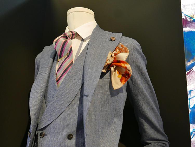 【GABRIELE PASINI】ガブリエレ パジーニらしい、大胆なビッグラペルのダブルスーツは、インパクトあるネクタイが似合う。ピンクのストライプタイはかなり目立つが、ストライプの一色はスーツと同系色にしているので自然に馴染んでいる。