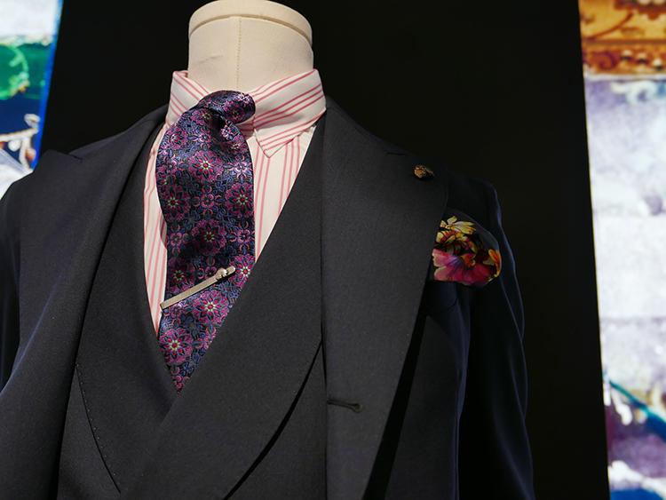 【GABRIELE PASINI】ネイビーの3ピーススーツを、いつもより華やかにしたいときは、ピンクカラーを挟んでみよう。ピンクストライプのタブカラーシャツは、色のトーン自体は淡めなので、合わせるネクタイは濃いめのパープル、ピンク系で。タブカラーとタイバーでグッとノットを上げれば、力強い第一印象になる。