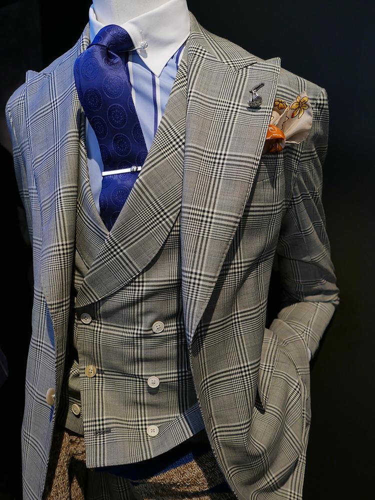 【GABRIELE PASINI】かなりインパクトのある大柄チェックの3ピーススーツ。実はシャツもネクタイも柄モノだが、シャツはかなり間隔広めのストライプ、またネクタイも織り柄無地にしているので、意外に喧嘩せずにまとまっている。クレリック×タイバーで、襟元に存在感をアップ。