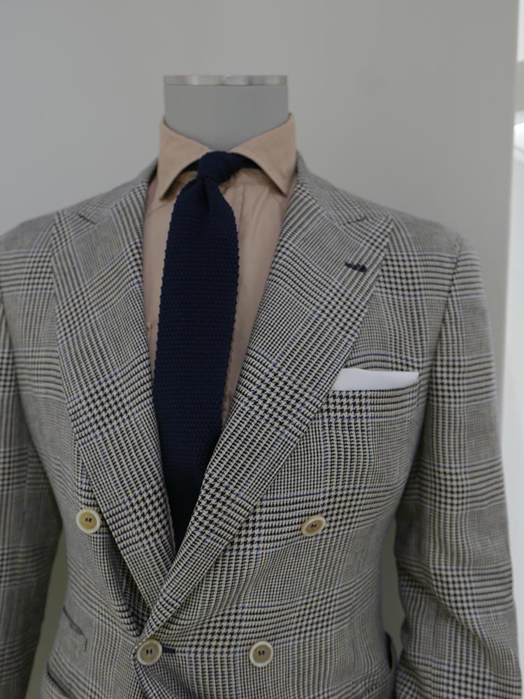 【BRUNELLO CUCINELLI】グレンチェックのダブルスーツは、ペーンのブルーを拾ってニットタイも紺無地に。ここでシャツを白でなく、ベージュ系にするとお洒落度が格段にアップ!