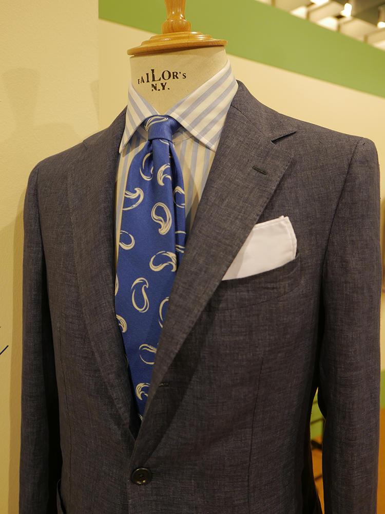【ERICO FORMICOLA】取り入れやすいネイビーグラデーションも、夏なら全体的に、淡めのブルートーンでまとめると涼し気でいい。ベースとなるスーツの紺も少し明るめ、またシャツのストライプの青もサックス系で爽やかに、ネクタイのロイヤルブルー系でコントラストを。ナポリブランドらしい、海を感じさせる美しい色合わせ。
