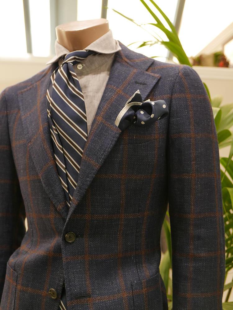 【TITO AREGRETTO】こちらもナポリのティト・アレグレット。紺×茶のチェックジャケットに、白シャツでなく淡いベージュのリネンシャツを合わせているのがお洒落度大。ネクタイも、紺×茶のストライプで色のトーンにまとまりがある。