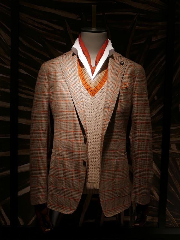 ラルディーニ。ブラウン×オレンジペーンのチェックジャケットは、インナーのニットのリブはスカーフ、チーフと随所にオレンジを散らして。