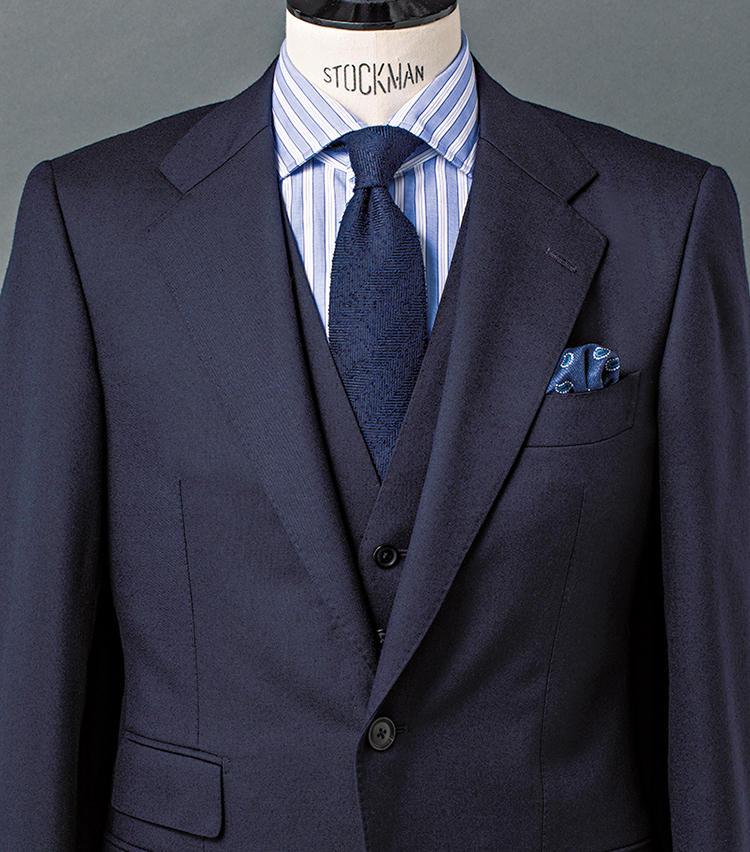 <b>2.ブークレ調ヘリンボーンタイで英国クラシックの趣を添える</b><br />ハリコシの強い、ネイビーのウールツイルを用いた3ピーススーツに、白×青の変則ストライプシャツを合わせた、旬の英国テイストが薫るスタイルだ。タイはブークレ調のネップを備えた、温かみあるシルクタイをセレクト。ヘリンボーンの織り柄も、英国然とした雰囲気を後押しする。さりげなく添えたチーフのペイズリー柄が、お茶目なアクセントに。