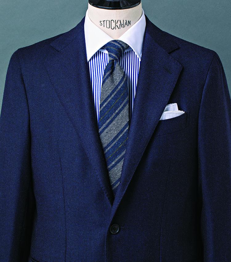 <b>4.レジメンタルタイ×クレリックシャツは、英国薫る鉄板コンビ</b><br />バーズアイ調の組織が浮かぶスーツ生地は、ほのかな起毛感がエレガンスの決め手に。シャツは白×青のロンドンストライプ柄のクレリックシャツをチョイス。そこへネップ感豊かなレジメンタルストライプタイを合わせることで、スーツとの素材感を調和させつつ、英国クラシックの薫りを際立たせた。落ち着きの中にさりげない主張を秘めたVゾーンだ。