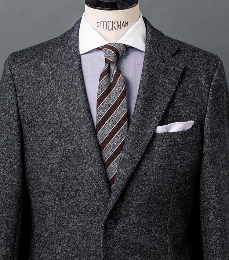 <b>2.メランジ調同士が織りなすシックにして趣満点のスタイル</b><br />黒と白が入り交じり、遠目にはチャコールグレーに見える生地のジャケットをベースに、英国テイスト薫るクレリックシャツ&レジメンタルタイをコーデ。タイはシルクウール素材で、ネップ感強め。シャツの身頃もシャンブレー生地で、こちらもメランジがかった色合いだ。色柄は控えめでも、メランジ調を組み合わせることでニュアンス満点に仕上がるのだ。