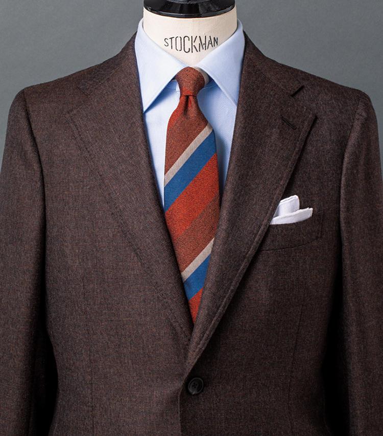 <b>4.ブラウンを基調に構築するトラッドが薫る温かなVゾーン</b><br />温かなブラウンベースのメランジ調スーツを軸にしたスタイル。シャツはスーツの素材感に合わせ、無地ながら程よい表情のあるドビーツイルの一枚をセレクト。そこへ褪せたような配色のレジメンタルタイを合わせ、古きよきトラッドの趣薫るVゾーンを構築している。タイのストライプ色でスーツやシャツの色を拾うのが、スマートに装うポイント。