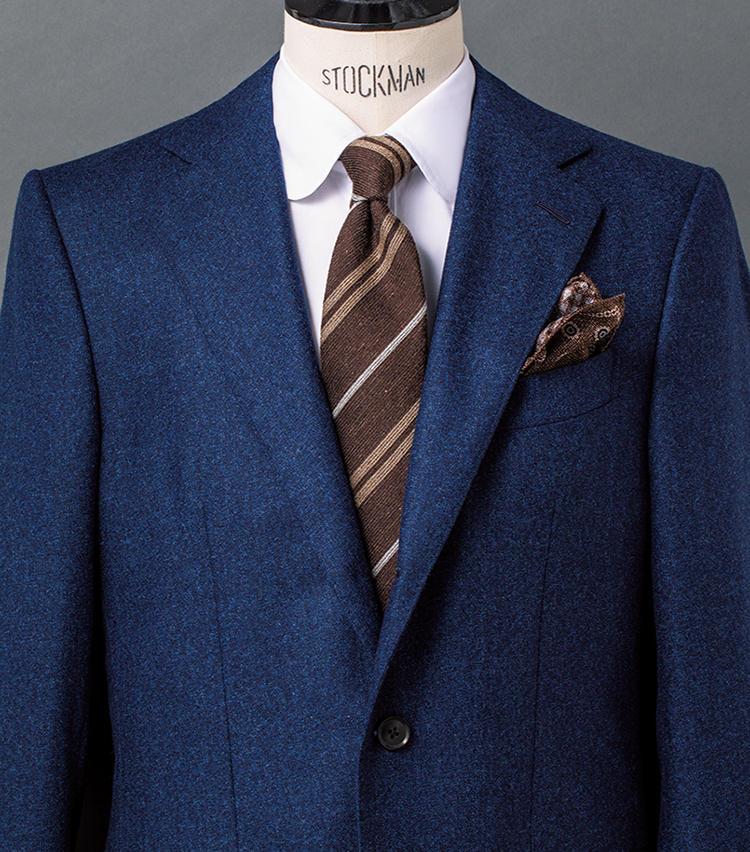 <b>5.鉄板のネイビー×ブラウンにメランジでさらなる奥行きを!</b><br />ネイビーとブラウンという相思相愛の2色をベースにした定番コーデも、メランジ調を意識してアイテムを選べば奥行きのある表情に。ここでは、青糸が交じるツイーディなネイビージャケットと、目の粗い風合い豊かなレジメンタルタイを合わせた。シャツはタイやチーフの色柄が引き立つ白無地。ただしラウンドカラーゆえ、フランクな趣も備わっている。