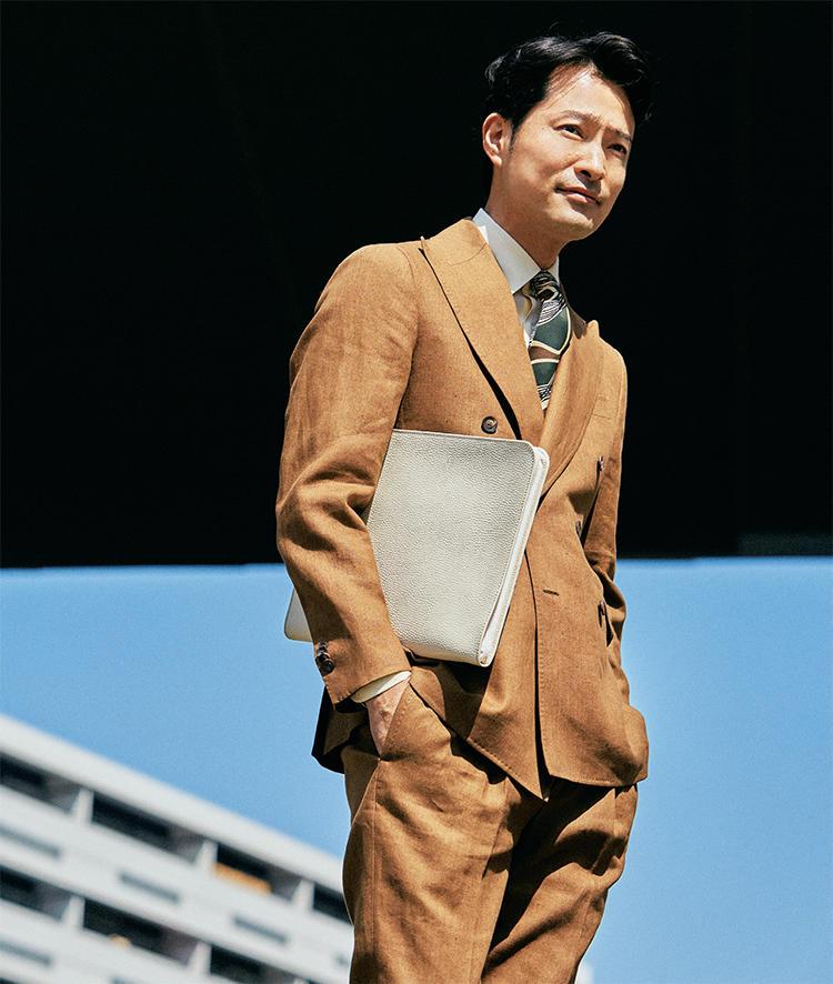 リネンスーツ×白のクラッチバッグを着用したモデル