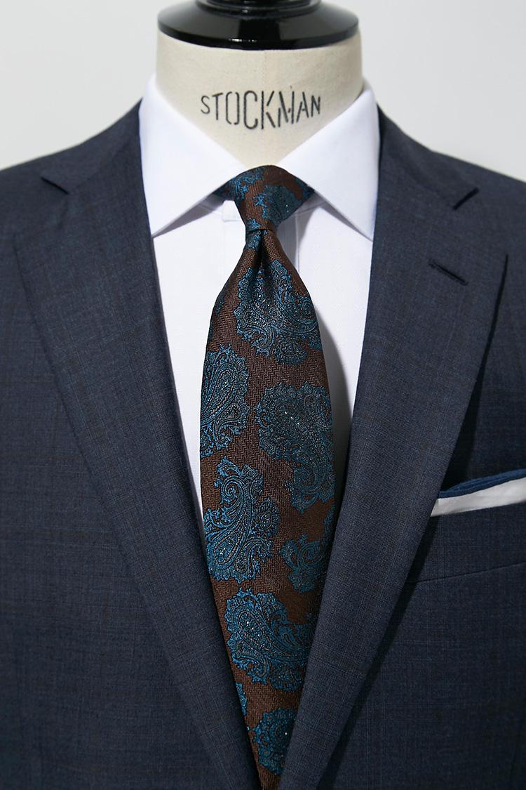 シャツが白無地の場合、ネクタイで少し遊んでみよう。大柄のペイズリー柄ネクタイも、派手色だと目立ちすぎてしまうが、このようにブラウン×ブルーのシックな色のトーンなら落ち着いて貫禄のある印象になる。スーツ13万円、チーフ5000円/以上ブルックス ブラザーズ