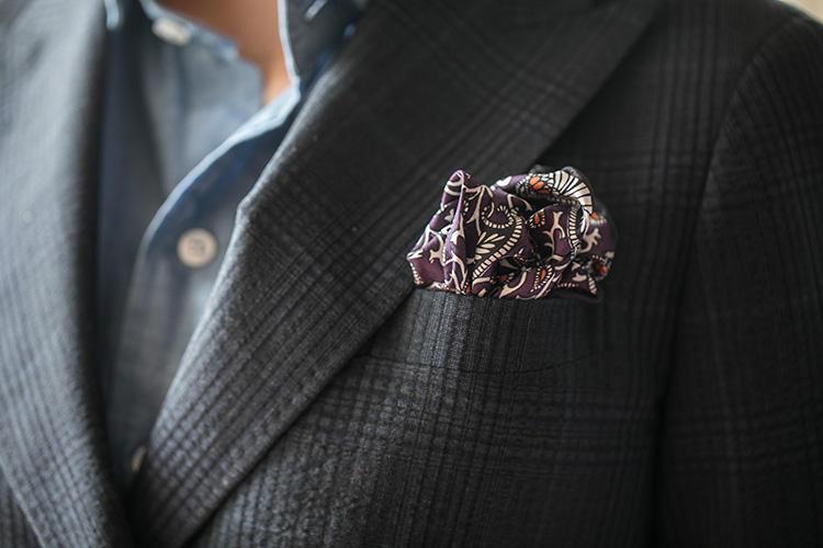 実際に挿すとこんな感じ。巻いた布が花びらのようにヒダを作って、普通のパフトよりも華やかな印象になるのがポイント。シルクのプリントチーフや薄手のコットン、カシミアなど、様々な素材で実践できるテクニックだ。