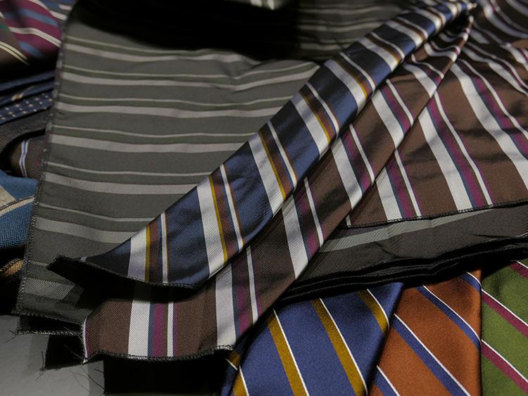同柄・色違いのネクタイ生地を複数重ね合わせて、ずらしながらタイの幅のように折っていく。