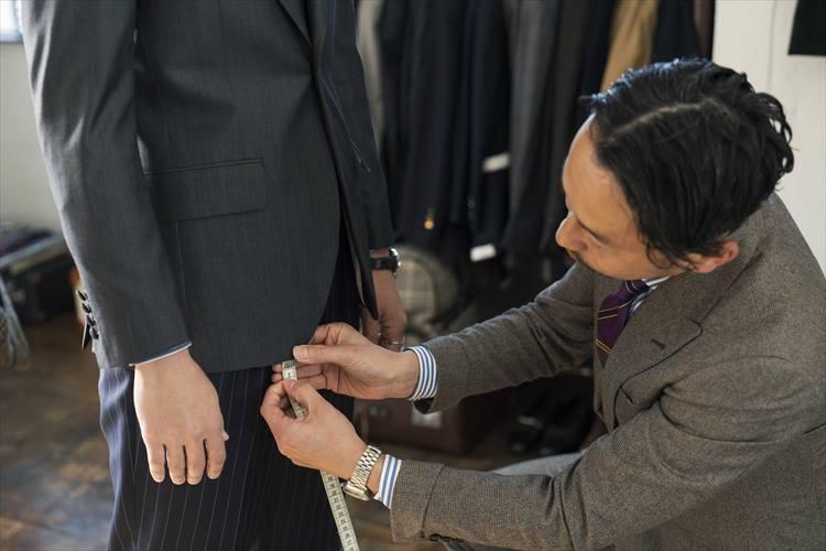 今回はオーダーサンプルよりも着丈を2cm長く設定。長谷川さんに、その差を伝えるためにメジャーをあてがう。