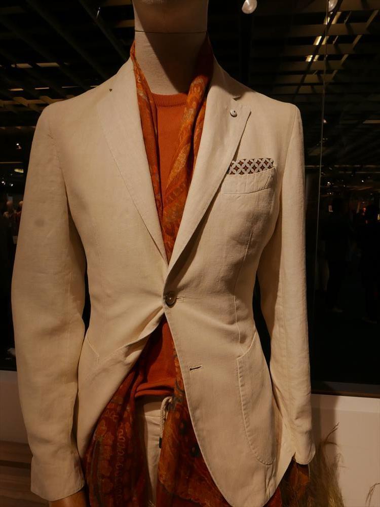 <strong>L.B.M.1911</strong><br />ハイゲージのクルーネックニットは、ノータイでスーツやジャケットを着るときの鉄板アイテム。写真のようなビビッドなオレンジは、休日のドレスダウンにも最適。間に同系色のスカーフを挟めば、さらにエレガントに。