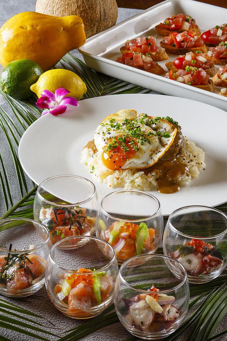 手前から:ポケ3種、ココモコ(ガーリックライスの上にハンバーググレービーソース、目玉焼き、キムチの天ぷらをのせた料理)、ロミアヒトースト(マグロのタルタルをトーストにのせたもの)