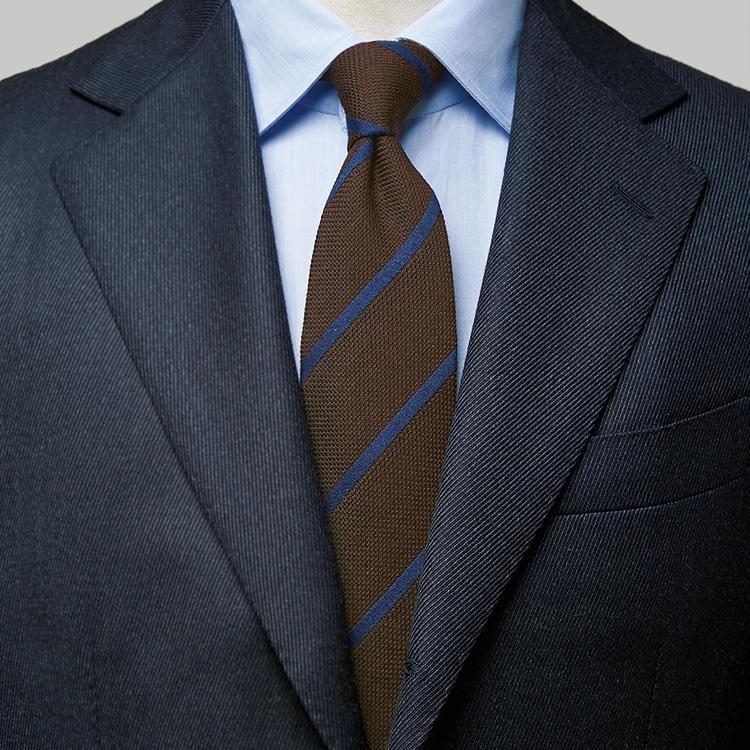 <p><strong>2位<br />いつもの紺スーツで、簡単にお洒落度を上げるには?</strong><br />いつもの紺スーツで、簡単にお洒落に見せるにはどんなシャツとネクタイを合わせるとよいか? ここで覚えておくと便利なのが、イタリア人もよく使う色合わせ「アズーロ エ マローネ」(イタリア語で紺×茶の意)だ。シャツは手持ちのサックスブルー無地でOK。ここに茶色の地色のネクタイを選ぶと良い。無地のブラウンタイでももちろん合うが、さらに洒落度を高めるなら、ブラウン地に紺色のストライプが入ったものを選ぼう。完璧なアズーロ エ マローネ配色で、シンプルながらひと目でお洒落な雰囲気に見せられる。<small>(2019年10月号掲載)</small></p>