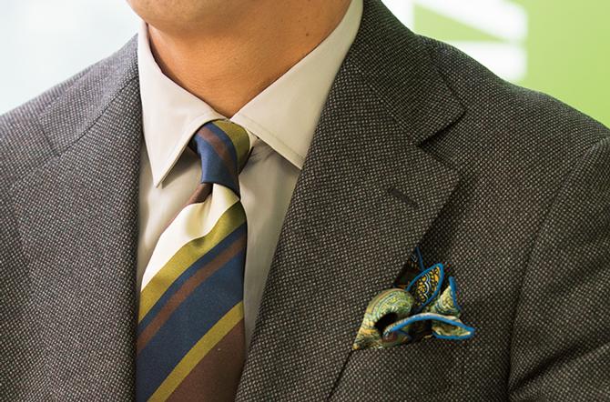 <p><strong>色を効かせる意識より馴染ませることで印象的に</strong><br />渋めのグリーンを軸に、シャツはベージュ、スーツはブラウンを合わせ、配色の美しさを狙う。さりげなく企業カラーを使うことで感度の高さを表現。</p>