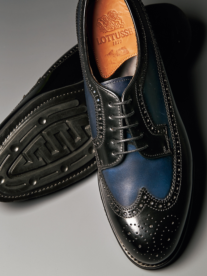 <p><strong>【LOTTUSSE / ロトゥセ】<br />都会的配色でカントリー靴を一新</strong><br /> ボリュームあるラウンドトウのウイングチップだが、張り出しすぎないコバや紺×黒の都会的配色によりモダンさが光る。紺の部分は職人が手で色を入れていて、味のあるアンティーク調のムラ感が魅力的だ。7万4000円(横浜髙島屋 6階 シューメゾン オム)</p>