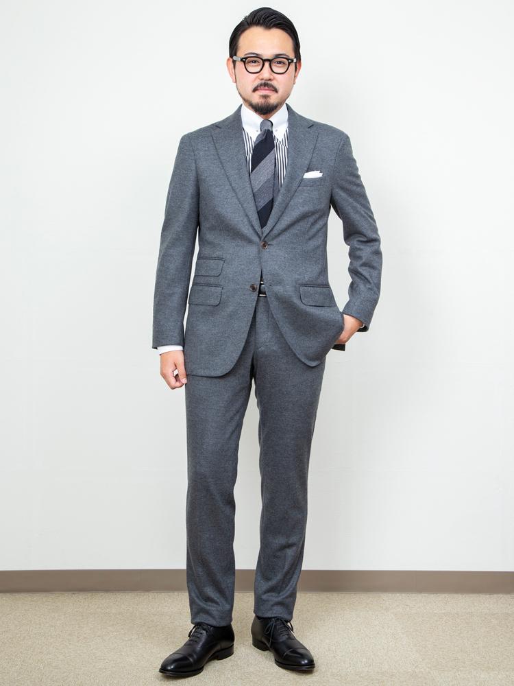 <p><strong>【着回し例・その1】きっちりしたビジネススタイル</strong><br /> ジャージー素材のセットアップを上下共生地でスーツとして着用。ストライプのクレリックシャツに同系色のレジメンタルタイと、色数を抑えつつクラシックなビジネススタイルに仕上げた。落ち着いた印象に合わせて、パンツの裾をハーフクッションにしている点にも注目。<figcaption>ジャケット<オーダー価格>4万円、パンツ<オーダー価格>2万円、シャツ<オーダー価格>1万3500円、ネクタイ9500円、チーフ1500円/以上、麻布テーラー</figcaption>