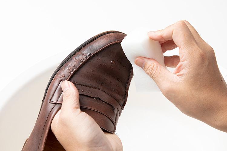 <p>ここでうっかりミス発生。本来はステインリムーバーで余計なクリームを落とすのだが、それを飛ばして水をつけてしまった。ちょっと不安になりながらも、後戻りはできないので続行。スポンジに水をつけ、靴に満遍なく水を浸透させていく。このとき、できるだけムラがないよう均等に濡らしていくことが重要だそう。それから、靴の内部まで水が染み込まないよう、アッパーだけを濡らすように注意。</p>