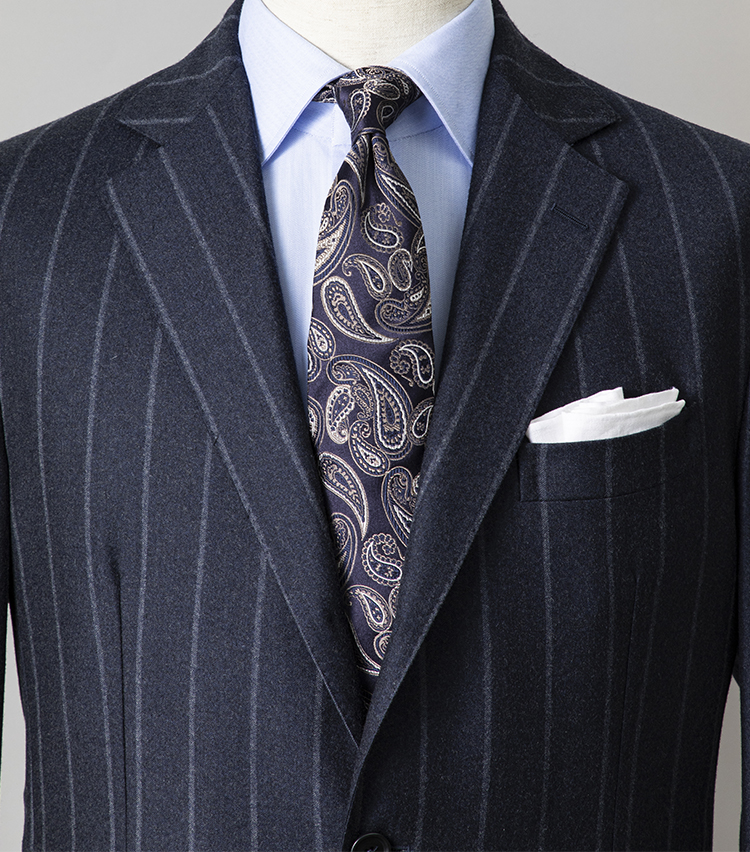 <p><strong>「派手柄」2種類を自然にまとめるコツは?</strong></br></p> <p>チョークストライプの紺スーツで威厳をアピールしつつ、ペイズリー柄のネクタイでミドルエイジらしい渋さをプラス。一見、難易度高めな派手柄同士のコーディネートも、シャツを同系色の無地にすればよく馴染む。ここではサックスブルーの無地シャツで、スーツとネクタイをリンクさせた。</p> <p><small>スーツ17万9000円/デ ペトリロ、シャツ2万4000円/ボリエッロ、ネクタイ1万6000円/フランコ バッシ、チーフ2300円/ビームスF</small> </p>