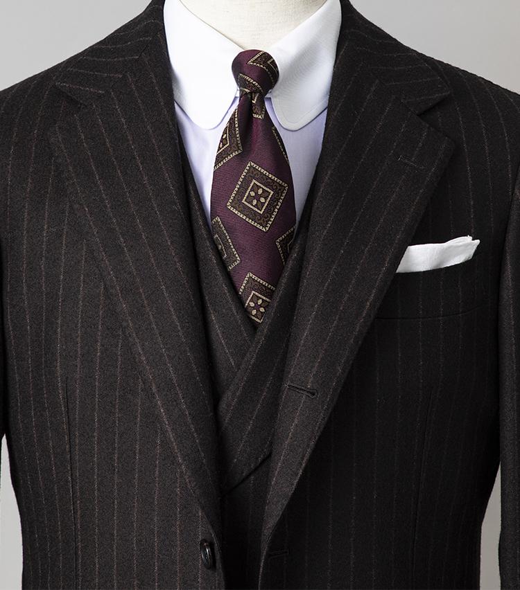 <p><strong>昼と夜、1着で見え方を変えるならどんなスーツ?<br /> </strong></br></p> <p>夜にパーティやレセプション、会食などが控えている日におすすめなのが、スリーピーススーツ。仕事中はベストなしで着用してシンプルに、パーティではベストを着込めば一気に華やぐ。ベストは襟付きのダブル仕様なら、よりドレッシーだ。ここではブラウンスーツと相性の良い、パープルのシャツとネクタイをコーディネート。ネクタイはヴィンテージ調の柄でトレンド感もプラスした。</p> <p><small>スーツ15万円/ブリッラ ペル イル グスト、シャツ3万6000円/アヴィーノ ラボラトリオ ナポレターノ、ネクタイ1万6000円/ホリデー&ブラウン、チーフ2300円/ビームスF</p> <p></small> </p>