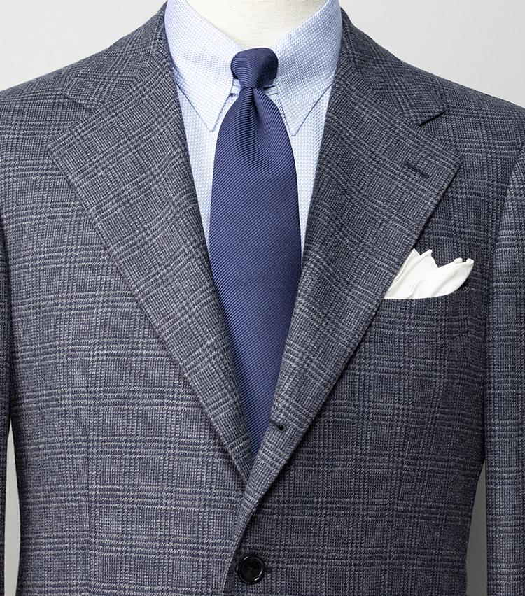 <p><strong>シャツタイともに無地でも、スタイリッシュに見せるには?</strong></br>優しげな淡色づくしのスーツスタイル。グレンチェック柄スーツを引き立てるべく、シャツとネクタイは無地を選んだが、シャツ生地は凝ったドビー織り、ネクタイはウール×シルク素材とひねりをきかせているため、無地づくしでも決してつまらなくは見えない。なお、スーツは英国老舗のジョシュアエリスの生地を使用しており、ワイドラペルがエレガントさを演出。このように品と旬の香るスーツを選ぶことも、シンプルスタイルで差をつけるコツだ。<br /> <small>スーツ12万円/ソブリン(ザ ソブリンハウス) シャツ2万8000円/エリコ フォルミコラ、ネクタイ1万4000円(以上ユナイテッドアローズ 六本木ヒルズ店) チーフ<スタイリスト私物><br /> </small></p>