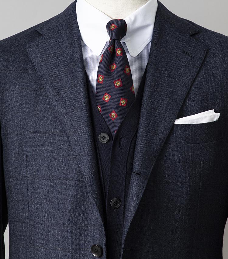 <p><strong>月朝の打ち合わせで好印象を与えるには?</strong></br><br /> よくある同系トーンのグラデーションコーディネートも、異素材アイテムを組み合わせればワンランク上の印象。ウールスーツ、コットンシャツ、シルクネクタイは、いずれも控えめな柄物というのも着ている人の品格が感じられる。このように柄物が多い場合は、柄のピッチをずらすことを心がけよう。スーツはシャドーウインドウペーン、シャツはかなり細かなグラフチェック。遠目には無地のようでいて、柄ピッチを広めと狭めにずらしているのがうるさくならないポイントだ。さらに無地のカーディガンを挟むと、柄が中和されてまとまりがグンとよくなる。<br /> <small>スーツ8万6000円、カーディガン2万円、チーフ2700円/以上シップス、シャツ2万6300円/エリコ フォルミコラ、ネクタイ2万1000円/ドレイクス</small></p>