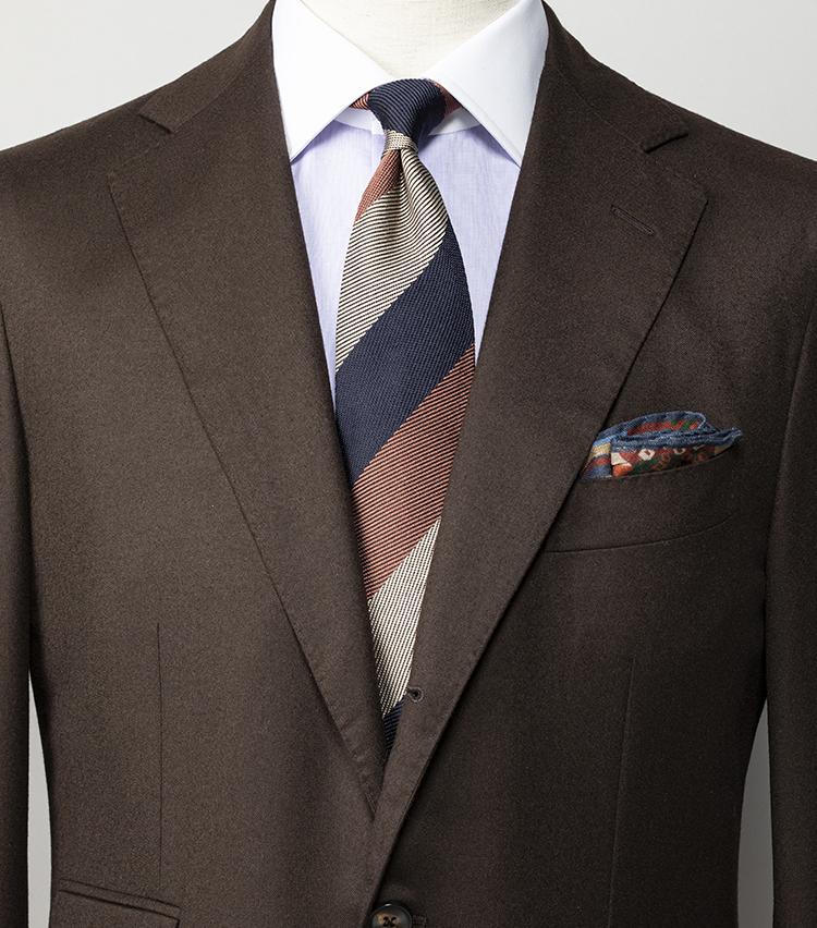 <p><strong>ブラウンスーツに似合うネクタイは? </strong></br><br /> ブラウンスーツにはブルー系の寒色のネクタイを合わせるのが王道だが、オレンジやベージュなどの暖色と柔らかい色調でまとめたほうが今季らしい。ライトサキソニー生地の柔らかなスーツは、イタリアの名門仕立てによるシップスエクスクルーシブブランドのもので、コストパフォーマンスの高さに定評がある。</p> <p><small>スーツ12万7000円/ヴァルディターロ ペル シップス、シャツ3万6300円/ルイジ ボレッリ、ネクタイ1万9000円/ニッキー、チーフ1万円/ドレイクス</small></p>